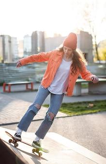 Volledig ontsproten jong meisje met buiten skateboard