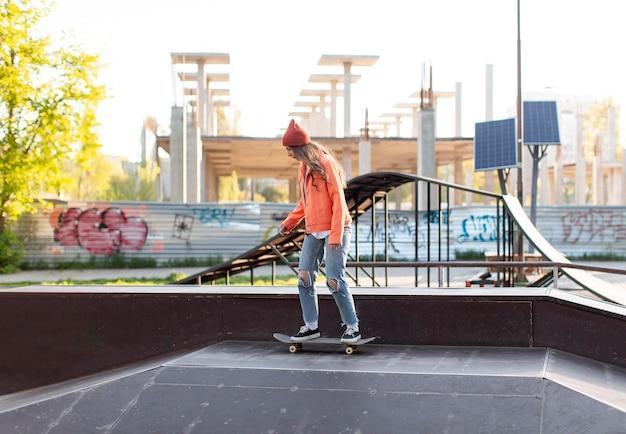 Volledig ontsproten jong meisje op skateboard buiten