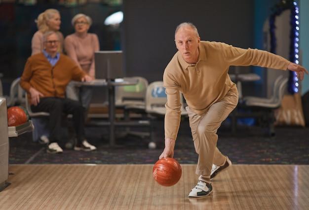 Volledig portret van actieve senior man die bowlen speelt en bal per baan gooit met een groep vrienden op de achtergrond, kopieer ruimte