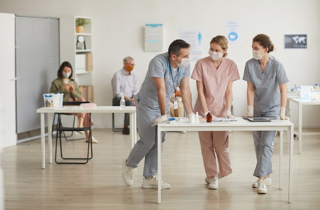 Volledig portret van drie artsen die maskers dragen die bij het bureau in de medische kliniek staan, kopieer ruimte