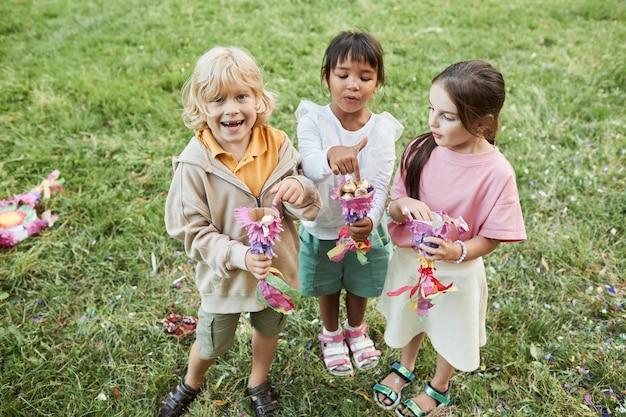 Volledig portret van drie schattige kinderen die snoepjes van pinata vasthouden tijdens een verjaardagsfeestje buitenshuis