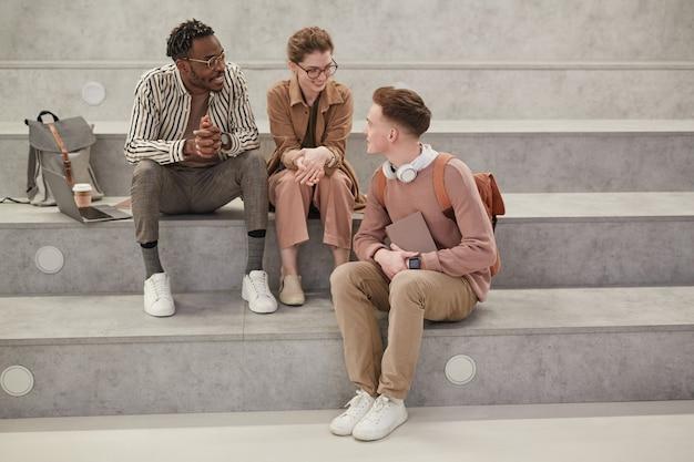 Volledig portret van drie studenten die chatten tijdens de pauze in de moderne universiteitslounge, kopieer ruimte