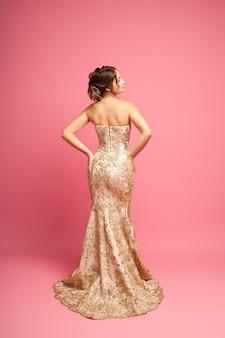 Volledig portret van een aantrekkelijke vrouw in een lange glanzende beige jurk en handen op haar heupen isola...