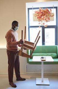 Volledig portret van een afro-amerikaanse man die een masker draagt in een café en meubels schikt terwijl hij zich voorbereidt op opening in de ochtend