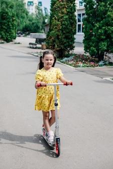 Volledig portret van een charmant meisje in een gele zomerjurk die op een scooter rijdt op een asfaltpad...