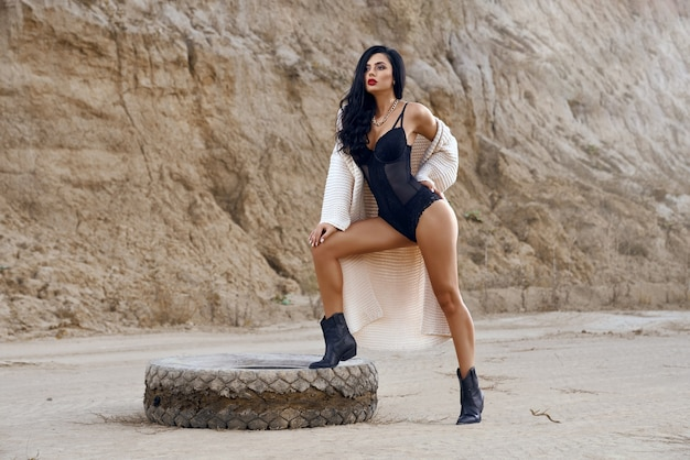 Volledig portret van een charmant vrouwelijk model met lang donker haar, gekleed in trendy bodywear, poserend in de woestijn in de buurt van oude banden