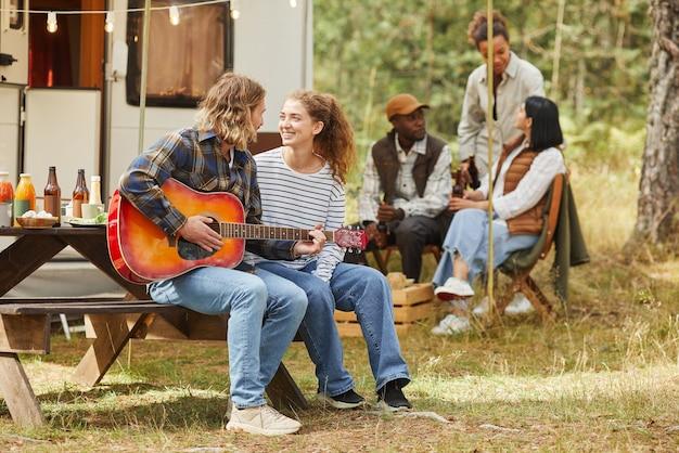 Volledig portret van een gelukkig jong stel dat gitaar speelt terwijl je geniet van buiten kamperen met trail...