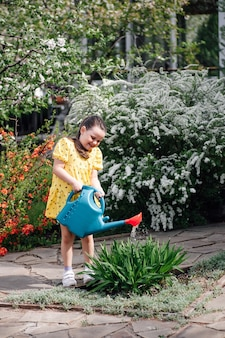 Volledig portret van een gelukkig meisje dat bloemen water geeft in een bloeiende lentetuin