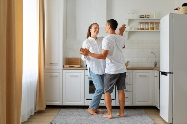 Volledig portret van een gelukkig positief verliefd stel dat samen in de keuken danst, samen tijd thuis doorbrengt en romantische gevoelens uitdrukt.