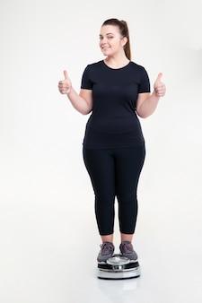 Volledig portret van een gelukkige dikke vrouw die op een weegmachine staat en duimen laat zien, geïsoleerd op een witte muur