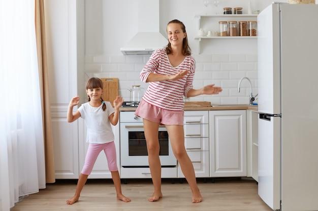 Volledig portret van een gelukkige moeder die zich geweldig voelt dansen met haar liefhebbende dochter, naar de camera kijkt, optimistische emoties uitdrukt, samen plezier heeft.