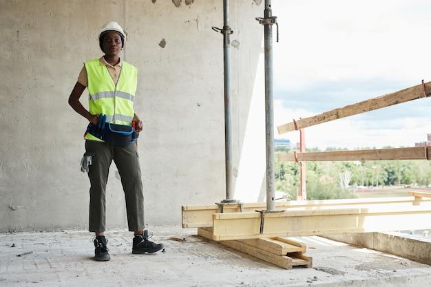 Volledig portret van een jonge afro-amerikaanse vrouw die op de bouwplaats werkt en glimlacht naar kwam...