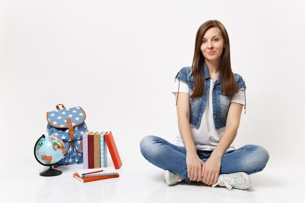 Volledig portret van een jonge, casual glimlachende studente in denimkleren die in de buurt van een wereldrugzak zitten, geïsoleerde schoolboeken