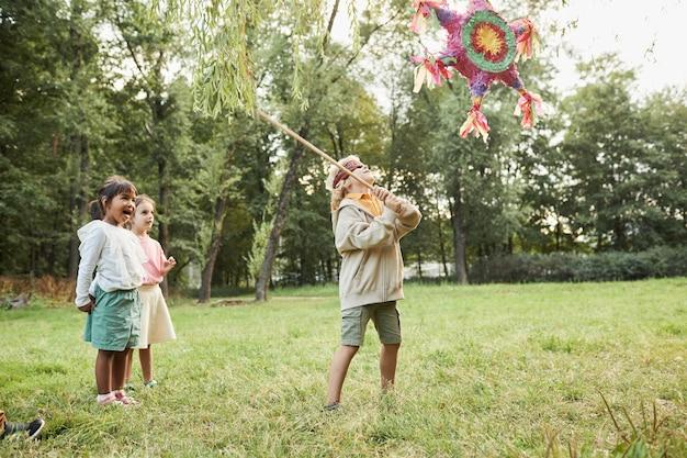 Volledig portret van een jongen die een pinataspel speelt op een verjaardagsfeestje in de buitenlucht en een vleermuiskopieerruimte vasthoudt