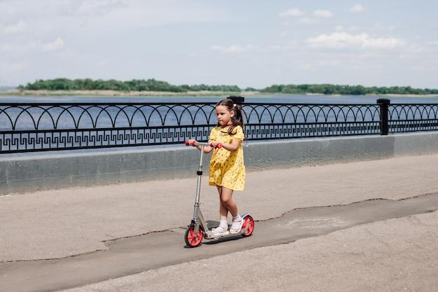 Volledig portret van een kind dat op een scooter rijdt op een asfaltdijk langs een gietijzeren hek in de stad...
