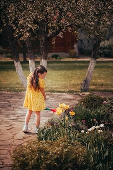 Volledig portret van een kind dat tuiniert in de achtertuin van een kind dat bloemen water geeft uit een water...