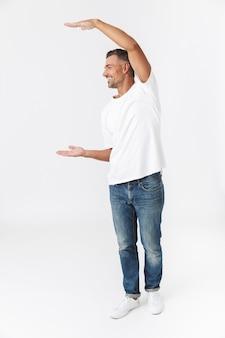 Volledig portret van een knappe, casual man die geïsoleerd op wit staat en kopieerruimte presenteert