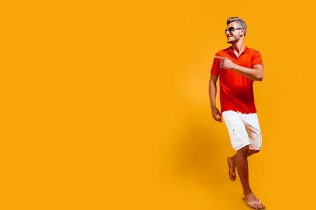 Volledig portret van een knappe man in korte broek en rood shirt die loopt en zijwaarts wijst met de vinger geïsoleerd op geel isolated