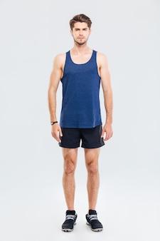 Volledig portret van een knappe man in sportkleding die geïsoleerd op een grijze achtergrond staat en naar de camera kijkt