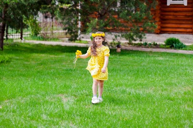 Volledig portret van een meisje in een gele jurk met gele paardenbloemversieringen die op de groene...
