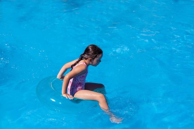 Volledig portret van een meisje in een roze zwempak dat schrijlings op een opblaasbare cirkel zit en een bal vasthoudt...