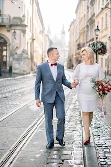 Volledig portret van een mooi verliefd stel van middelbare leeftijd, wandelend in elegante kleding buiten in de prachtige oude europese stad. vrouw in witte jurk houdt bloemboeket vast