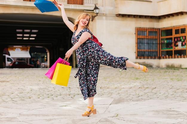 Volledig portret van een mooie en gelukkige vrouw die kleurrijke boodschappentassen vasthoudt terwijl ze buiten op straat springt van vreugde