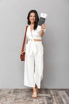 Volledig portret van een mooie jonge brunette vrouw die een zomeroutfit draagt die geïsoleerd over een grijze muur staat en een paspoort met vliegtickets toont