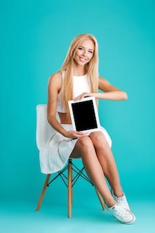 Volledig portret van een mooie jonge vrouw die een tablet met een leeg scherm toont terwijl ze op een stoel zit geïsoleerd op de blauwe achtergrond