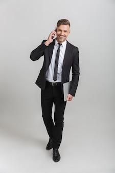Volledig portret van een mooie volwassen zakenman in een kantoorpak die een laptop vasthoudt en op een smartphone praat terwijl hij geïsoleerd staat
