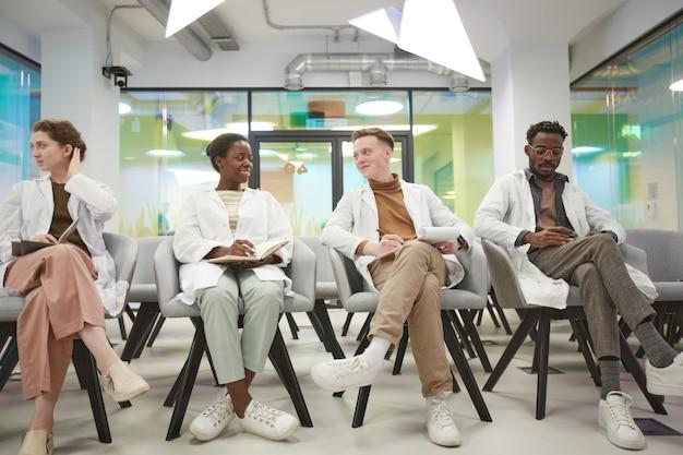 Volledig portret van een multi-etnische groep glimlachende mensen die laboratoriumjassen dragen terwijl ze in de rij zitten en luisteren naar een lezing over geneeskunde op de universiteit, kopieer ruimte