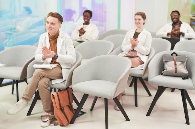 Volledig portret van een multi-etnische groep mensen die applaudisseren terwijl ze in het publiek zitten en luisteren naar een lezing over medicijnen op de universiteit of een coworkingcentrum, kopieer ruimte