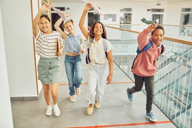 Volledig portret van een multi-etnische groep schoolkinderen die maskers vasthouden en vrolijk glimlachen terwijl ze binnenshuis naar de camera lopen