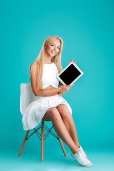 Volledig portret van een opgewonden blonde vrouw die een tablet met een leeg scherm toont terwijl ze op een stoel zit geïsoleerd op de blauwe achtergrond