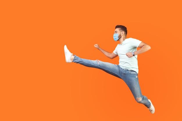 Volledig portret van een opgewonden man met chirurgisch medisch masker in casual stijl die in de lucht springt, snel snel rent, haast heeft voor kortingen. indoor studio-opname geïsoleerd op oranje achtergrond