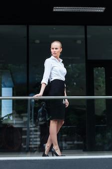 Volledig portret van een serieuze zakenvrouw die buiten staat en op de glazen balustrade leunt