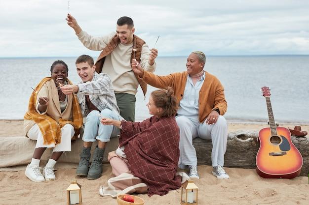 Volledig portret van een trendy groep jonge mensen die in de herfst genieten van een feestje op het strand en s...