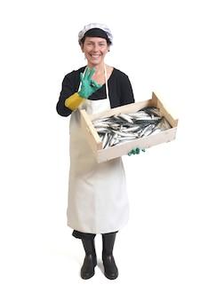 Volledig portret van een visboer die een doos sardine vasthoudt en een goed teken op een witte achtergrond