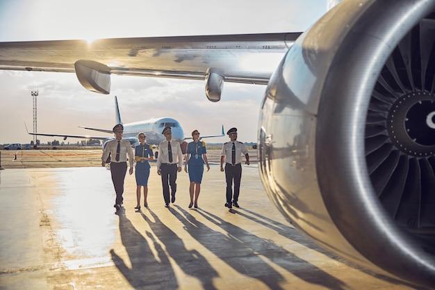 Volledig portret van een vluchtteam met een zakelijk uniform dat in de buurt van het passagiersvliegtuig in de buitenlucht loopt