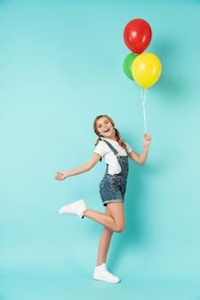Volledig portret van een vrolijk klein meisje geïsoleerd over blauwe muur, met een stel kleurrijke luchtballonnen, poserend