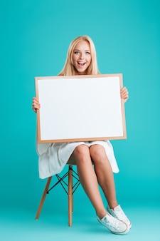 Volledig portret van een vrolijke glimlachende vrouw die een leeg bord vasthoudt terwijl ze op een stoel zit geïsoleerd op de blauwe achtergrond