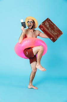 Volledig portret van een vrolijke, shirtloze man met opblaasbare ring en zonnebril, paspoort tonend, koffer geïsoleerd dragend