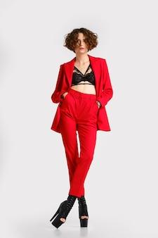 Volledig portret van een vrouw in rode pantsui en paaldanslaarzen staat met de handen in de zakken