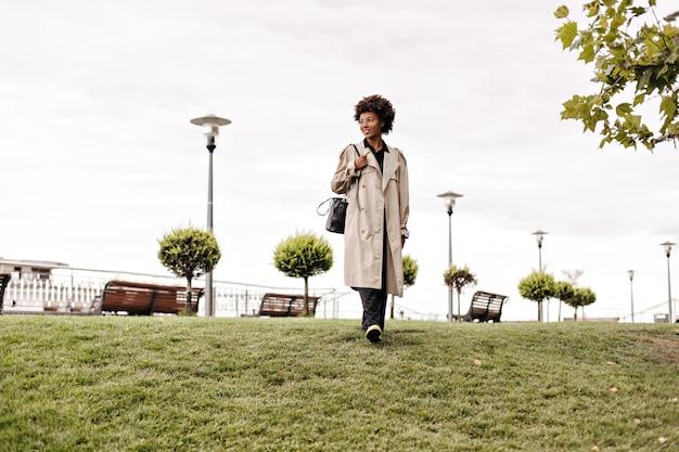Volledig portret van een vrouw met een donkere huidskleur in een beige oversized greppel en een zwarte broek die in het park in de buitenlucht loopt