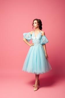 Volledig portret van elegante jonge vrouw in blauwe avondjurk met volledige rok en lantaarnmouwen...