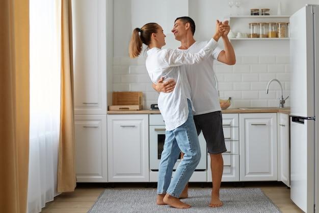 Volledig portret van gelukkig lachende man en vrouw die samen dansen thuis in lichte kamer, met keukenset, koelkast en raam op de achtergrond, gelukkig paar.