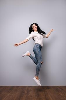 Volledig portret van gelukkig lachende springende vrouw die opgewonden is omdat ze alle examens aan de universiteit heeft gehaald