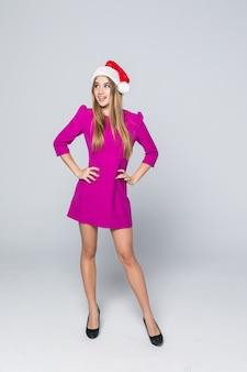 Volledig portret van glimlachen mooi meisje met gouden haren in roze jurk en nieuwe jaar hoed op wit wordt geïsoleerd