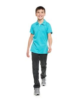 Volledig portret van glimlachende lopende tienerjongen in blauwe casuals t-shirt geïsoleerd op wit.