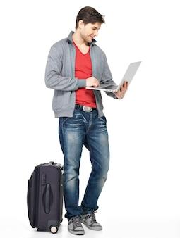 Volledig portret van jonge glimlachende gelukkige die mens met koffer en laptop op wit wordt geïsoleerd